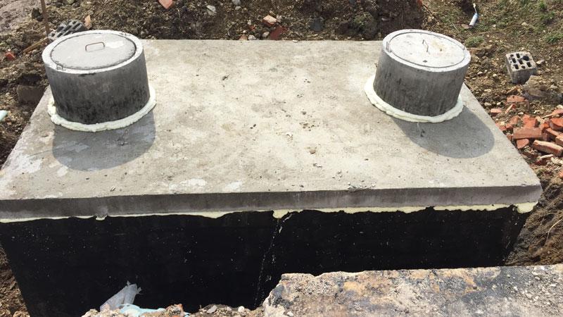 Dvojkomorová betónová žumpa, pripravená na pripojenie potrubia
